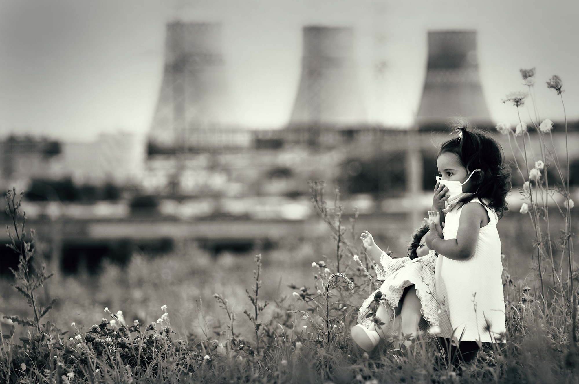 Young girl in respiratory mask holding doll in front of smokestacks